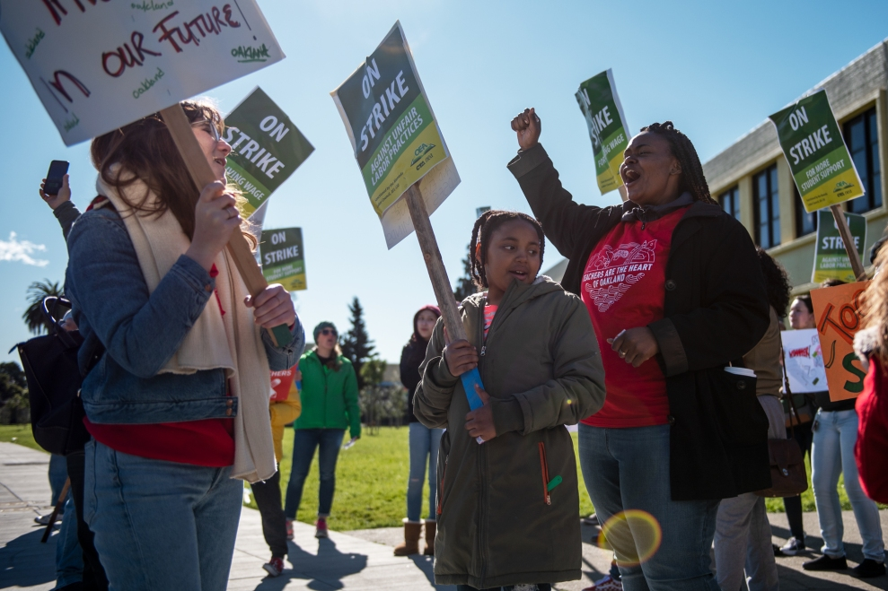 Magdaline Armstrong (right), a first grade teacher, and her daughter Nilaya, 8, rally on a picket line with kindergarten teacher Grace Allen (left) outside Lockwood Elementary School in Oakland, Calif., on February 21, 2019.