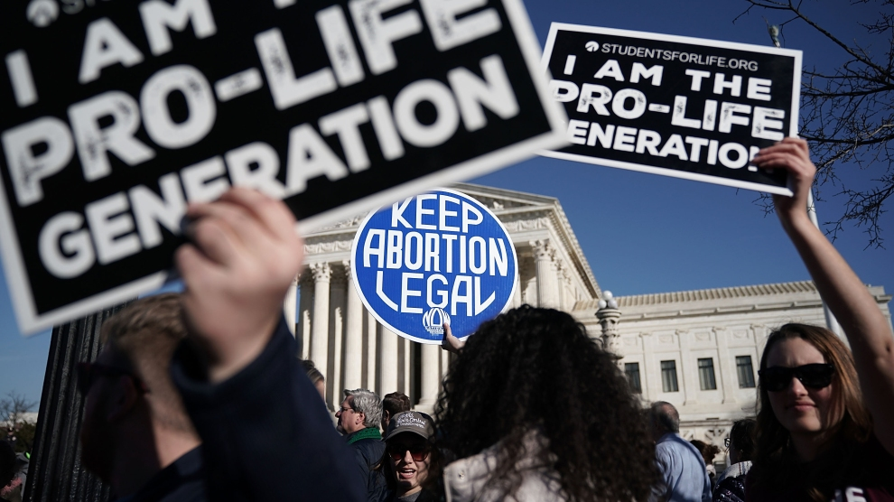 Pro-life activists try to block the sign of a pro-choice activist during the 2018 March for Life January 19, 2018 in Washington, DC.