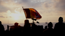 The American Indian Movement flag flies with an upside down American flag with the sunrise and SF Bay Bridge in the background.