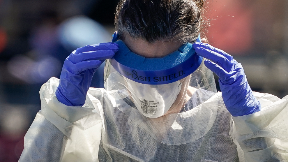 A worker in an N-95 mask, gloves, cover-alls, and a face shield on their eyes.