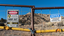 """With heaps of rock in the background, signs on a gate read """"Abandoned Uranium Mine, Keep Out"""" with the symbol for radioactivity."""