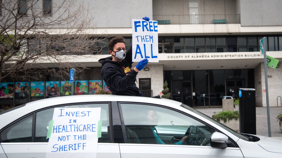 """A protestor in sweatshirt, cloth sick mask, and dark gloves holds a sign out the sunroof of a car, reading """"FREE THEM ALL."""""""
