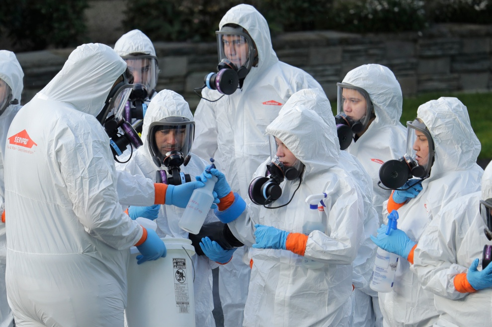 Workers from a Servpro disaster recovery team wearing protective suits and respirators are given supplies as they line up before entering the Life Care Center in Kirkland, Wash., March 11, 2020.