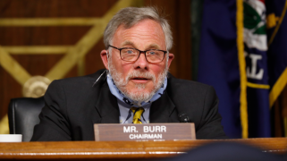 Sen. Richard Burr, with a gray beard and glasses, speaking behind a nameplate in a Senate chamber, with a mask pulled down around his chin.