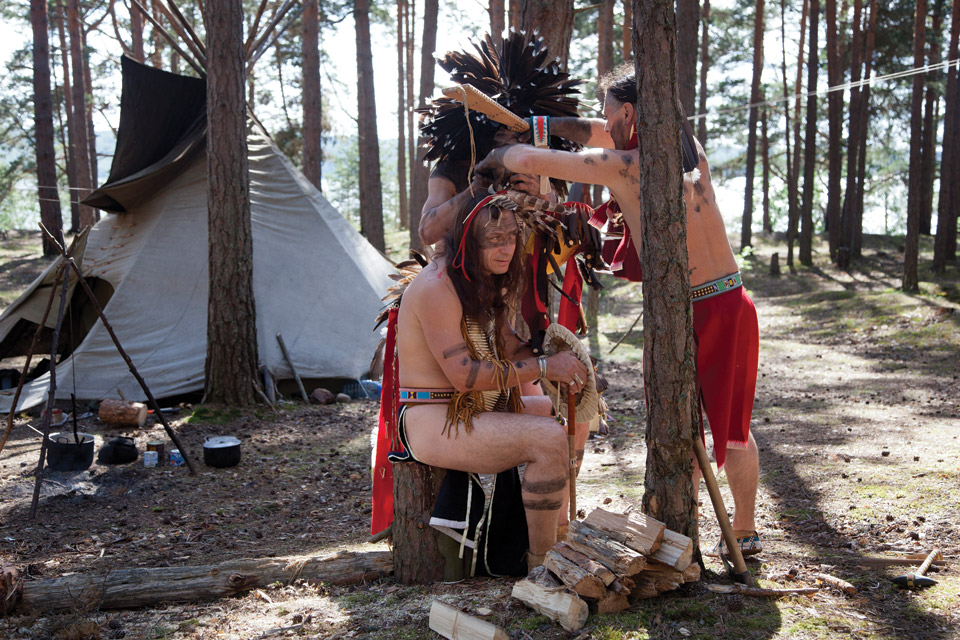 Man dressed as Native American being fitted with feather headdress.