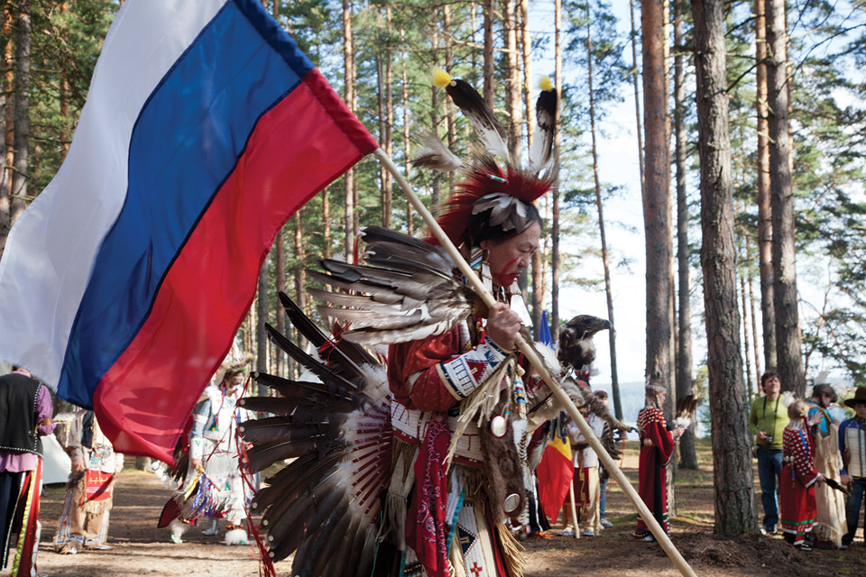 Man dressed as Native America carring a flag.