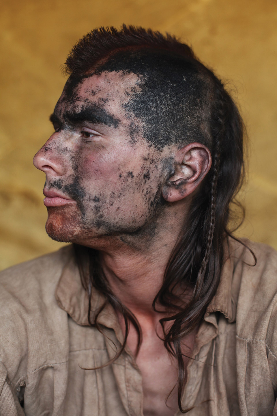 Man dressed as Native American with mohawk and braid.