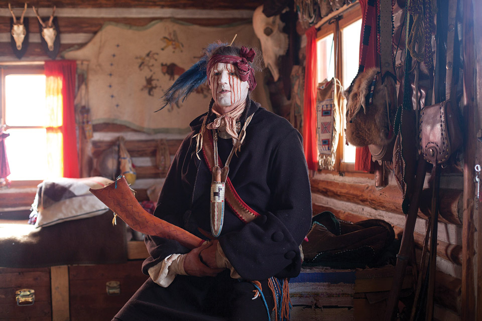 Man dressed as Native American with face paint.