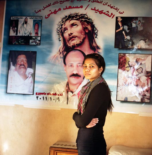 Mariam Musaad stands in front of a picture arrangement showing her father's body as it was brought to the Coptic Hospital morgue following clashes between civilians and the army near the Maspero TV building on October 9, 2011. The photographs and posters have become a permanent memory installation in Mariam's living room.