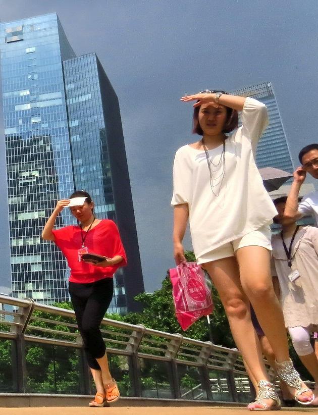 Pedestrians in Shanghai cover themselves from the scorching sun on August 6, 2013.